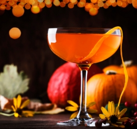 orange cocktail with fall backdrop